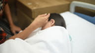 Sick little girl sleeping on the bed , child with a fever and woman stroking the child's head at the hospital