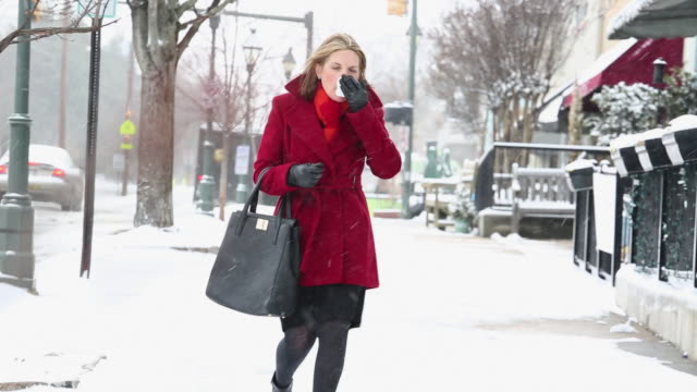 WS PAN Sick Woman Blowing Nose in Snow on City Street / Richmond, Virginia, United States