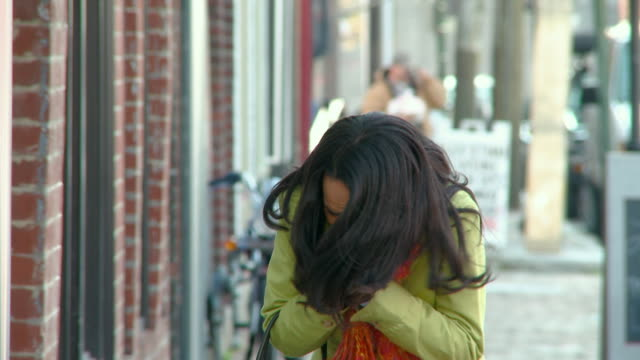 CU, Sick woman coughing and sneezing into tissue on street, Richmond, Virginia, USA