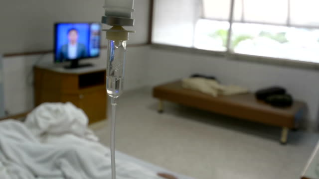 A sick woman lays in a hospital bed behind an IV drip chamber.