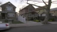 Side Angle  hand-held tracking-right - Houses line a neighborhood street in the Bronx. /  New York City, New York, USA