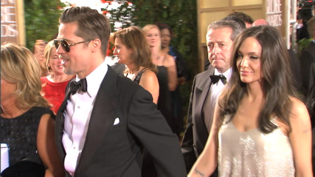 side angle MCU Brad Pitt and Angelina Jolie walking red carpet Angelina smiles waves and nods as Pitt looks in opposite direction