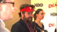 HD side angle MCU rack focus between Zach Galifianakis and John Hodgman talking to reporters along the red carpet