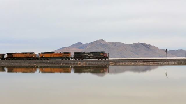 Side angle of train tracks on the Great Salt Lake as a train cuts into frame