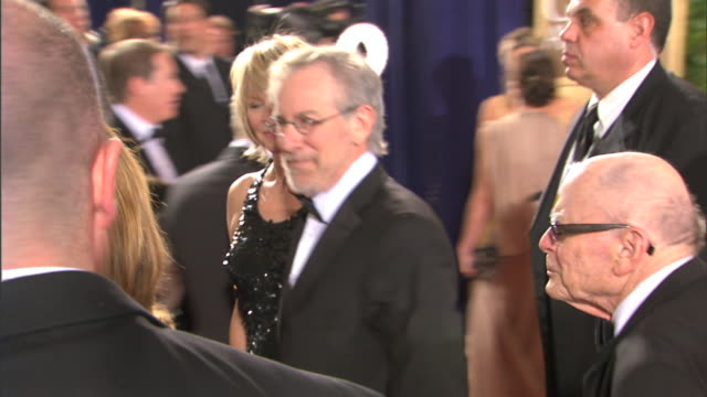 side angle Steven Spielberg waving as he walks with Kate Capshaw down red carpet