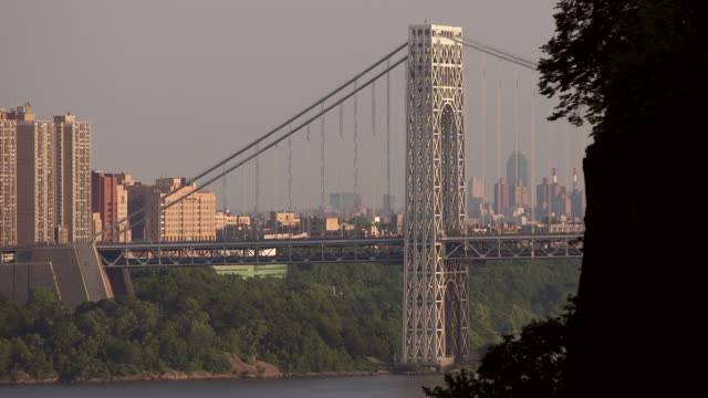 Side angle view of the George Washington Bridge taken from the Palisades in New Jersey.  Harlem is behind at the end of day.