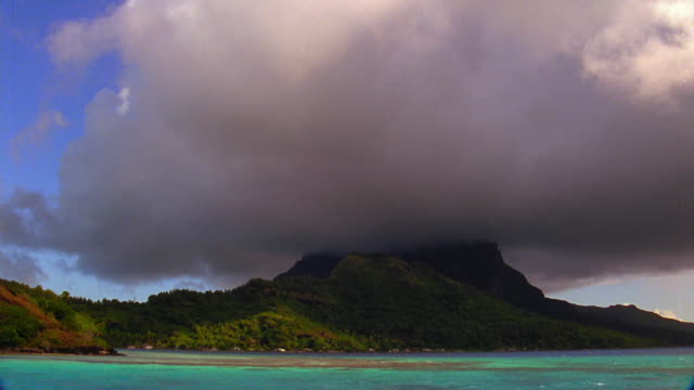 Side boat point of view low storm clouds covering rocky island / Bora Bora, French Polynesia, South Pacific