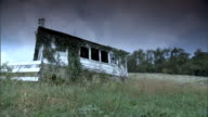 Side of abandoned dilapidated barn or small house w/ weeds growing around structure some broken windows grass field trees BG cloudy sky PA rural...