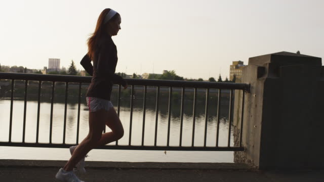 MS Side POV SLO MO Shot of beautiful female jogger on city water front park at sunset / Portland, Oregon, United States