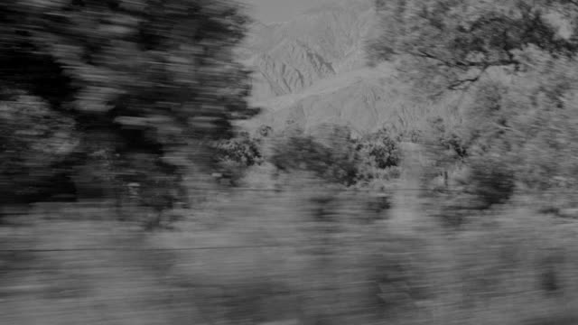 WS Side POV Shot of Car driving through Near Lone Pine with mountains