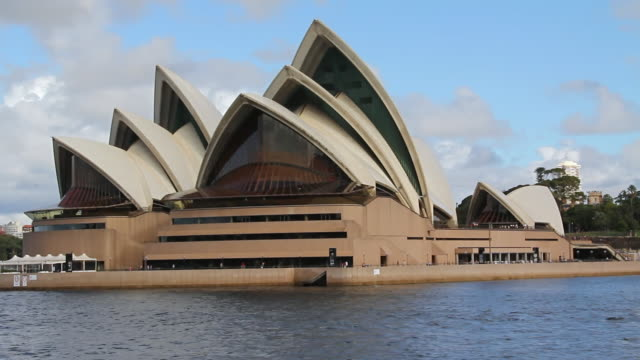 MS Side POV TS Shot of  Sydney Opera house with moving boats and back side buildings / Sydney, Australia