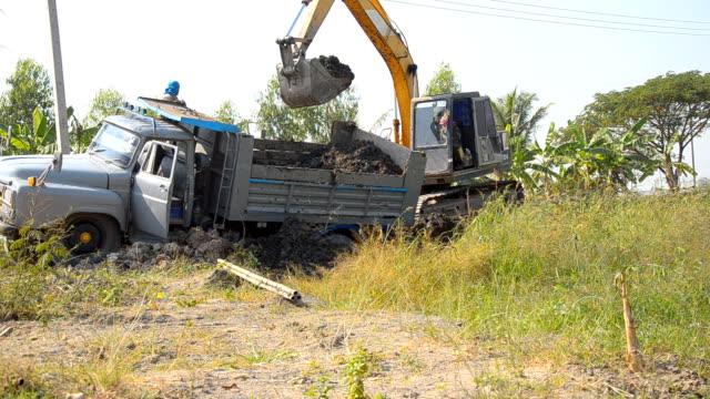 Seitenansicht: Bulldozer dig Erde aus einem LKW