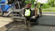 MS Side View of asphalt laying machine moving ahead on resurfacing of road and workers working / Saarburg, Rhineland-Palatinate, Germany