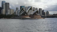 WS Side POV TS View of  Sydney Opera house with moving boats and back side buildings / Sydney, Australia