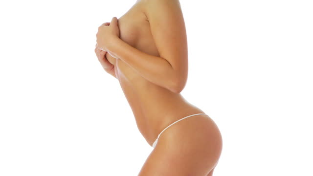 Side view of woman in white underwear holding breasts