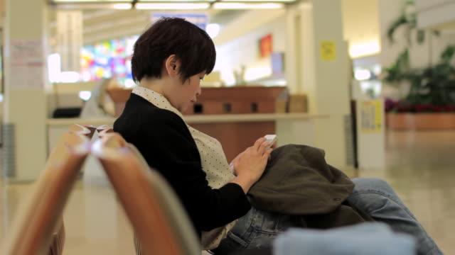 MS Side View of woman using smartphone at airport / Haneda, Tokyo, Japan