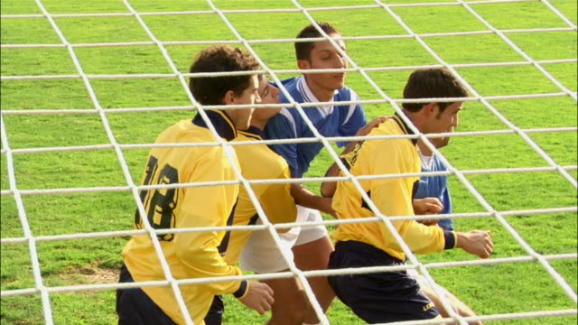 Side view soccer players jostling before corner kick / player heading ball into goal