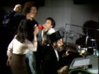 Side view Weird Al Yankovic among a group of people dance around playing kazoos and other toy instruments as Dr Demento introduces his radio show in...