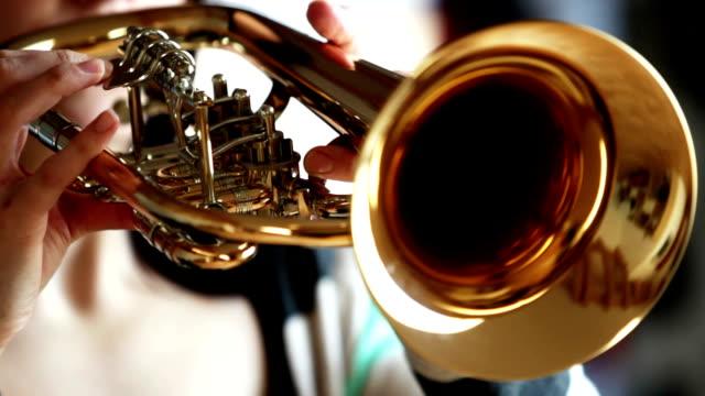 Seiten-Ansicht von Frau spielt Flügelhorn/Trompete