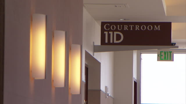 A sign above a door reads, Courtroom 11D.