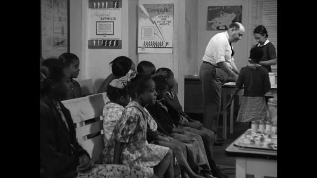 Sign 'Colored Department' INT WS NegroAmerican children sitting on bench in public health office MS Doctor examining BlackAmerican girl CU Girl w/...
