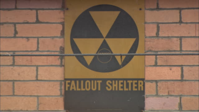 A sign for a fallout shelter hangs on a brick wall.