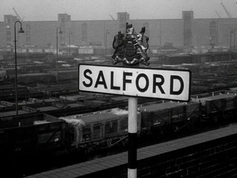 A sign for Salford over looks a train depot