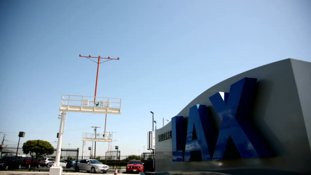 WS 'LAX' Sign frame w/ traffic moving on highway BG jet airplanes flying low OVERHEAD descending toward frame CA