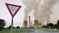 WS T/L Sign Give Way in front of a Loy Yang power station emitting pollution and carbon dioxide (CO2) into atmosphere contributing to global warming, climate change in Yallourn at Latrobe Valley / Morwell, Victoria, Australia