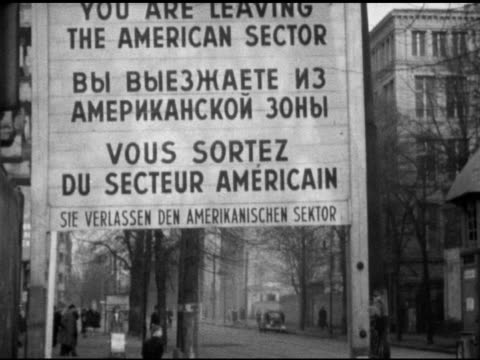 Sign in English German French 'You Are Leaving The American Sector' tour bus driving up street in West Berlin pedestrians BG INT MS Tourists riding...