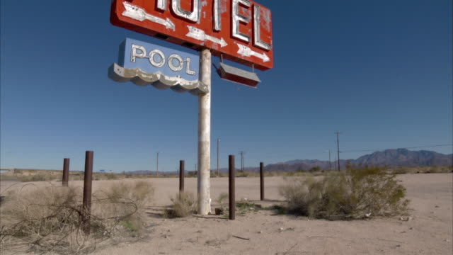 A sign in the Arizona desert advertises a motel with a pool.