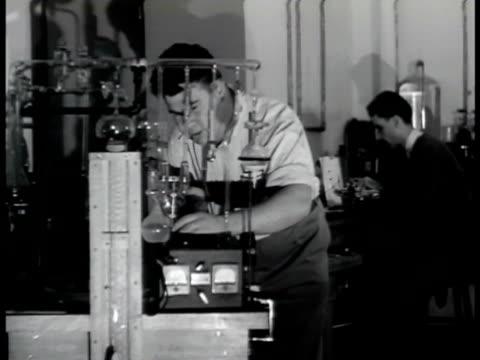 Sign Naval Research Lab Chemist scientist w/ liquid in large round beaker Chemist w/ small beakers Man looking into oscilloscope Man working w/ radio...