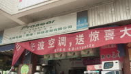 MS Sign of appliance retailer/ TD WS Man walking into shop/ Subei, China