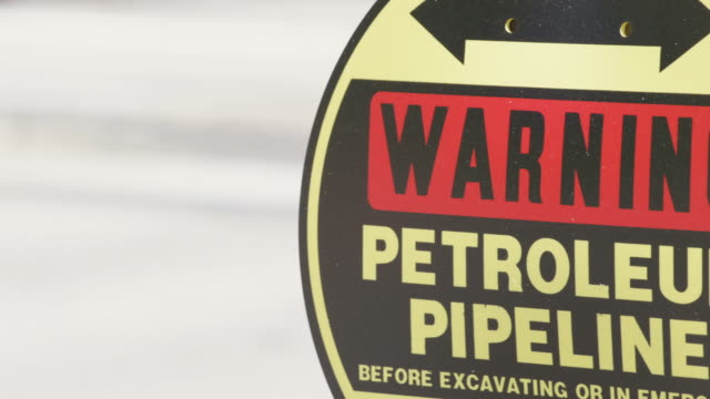CU Sign of declaring Warning Petroleum Pipeline with reflections of nearby passing cars / Beaverton, Oregon, United States