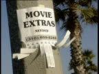 Sign stuck on concrete pillar advertising 'Movie extras needed'. Tear off telephone numbers flapping in breeze palm trees in background. Venice Beach