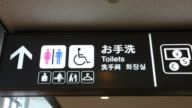 CU PAN Sign to restroom and currency exchange in English and Japanese script / Tokyo, Japan