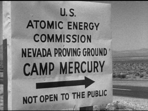 Sign 'US Atomic Energy Commission Nevada Proving Ground Camp Mercury' PAN TO WS Car turning down dirt road Angled WS Car pulling up to US Soldier in...
