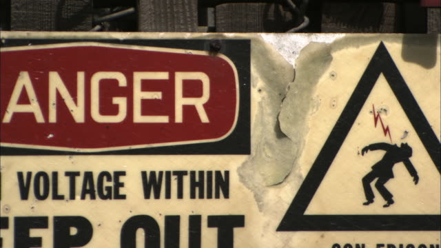 A sign warns of high voltage at a power plant.