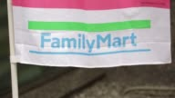 Signage for FamilyMart Co is displayed on a banner outside a convenience store in Tokyo Japan on Saturday March 7 Pedestrians walk past a FamilyMart...