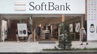 Signage for SoftBank Group Corp is displayed at a store in Tokyo Japan on Tuesday July 26 Pedestrians walk past a SoftBank Group Corp store in Tokyo...