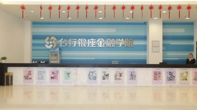 Signage is displayed inside the Bank of Taizhou's headquarters in Taizhou China on Tuesday Nov 7 Newly recruited employees dressed in fatigues walk...