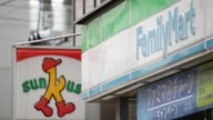 Signages for FamilyMart Co convenience store right and Sunkus convenience store operated by Circle K Sunkus Co a subsidiary of Uny Group Holdings Co...
