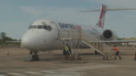 signs at Broome airport terminal arrivals lounge / person signalling plane / ground staff preparing for disembarking chocks under wheel / close up...