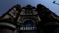 Signs in an archway identify Leeds City Market. Available in HD.