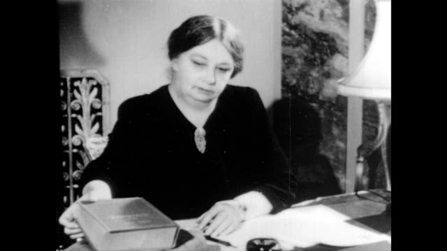 / Sigrid Undset Nobel Prize winner for literature sits at her desk reading / begins writing in notebook / consults book and continues to write Sigrid...