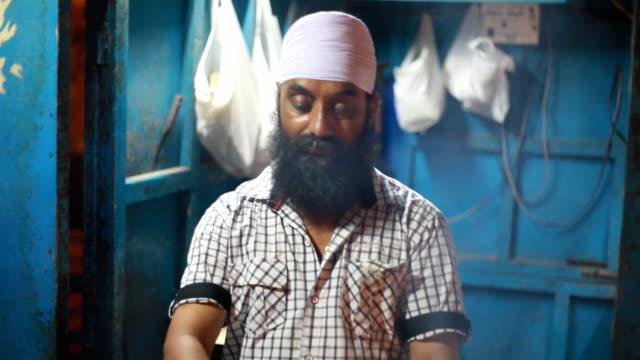 Sikh Mann Vorbereitung der verschiedenen Gegrilltes Tandoori-Huhn in Delhi, Indien