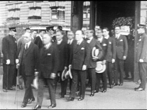 Silent film actress Pola Negri being escorted from funeral home into waiting car pallbearers walking w/ casket of Silent film star Rudolph Valentino...