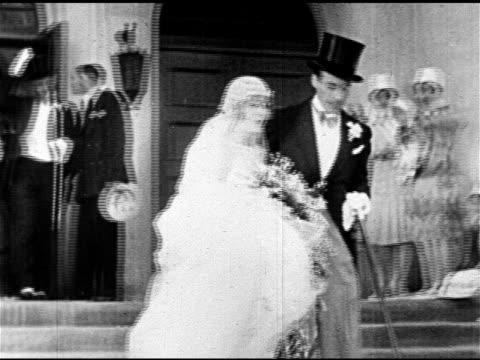 Silent film actress Vilma Banky walking out of church w/ actor Rod La Rocque standing outside smiling talking