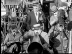 1924 B/W MS Silent movie director (Vernon Dent) shouting into megaphone, while cameraman (Andy Clyde) films action and another man (Charles Murray) watches / USA