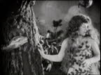 A silent movie reenacts Adam and Eve in the Garden of Eden and the serpent's attempt to tempt Eve